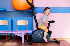 A small baby sits on an exercise bike in the gym royalty free stock photo