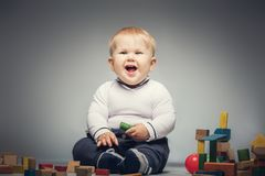 Giggling child sitiing on the floor with toys. Little kid sitting on the floor, with building blocks around him, smiling and giggling Stock Images