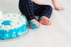 Little kid sitting near white cake, touching it with his hands and trying to taste it. The child has dirty hands and pants from th