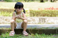 Little kid sitting in the park Stock Photos