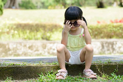 Little kid sitting in the park Stock Photography