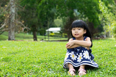 Little kid sitting in the park Stock Images