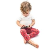 Little kid sitting and playing smartphone Stock Photos