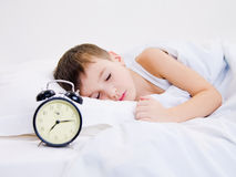 Little kid sleeping with clock near his head royalty free stock photography