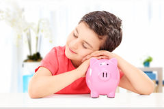 Little kid sleeping on a piggybank indoors Royalty Free Stock Photos