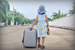 A little kid with a suitcase escape from house Stock Images