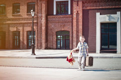 Little kid with suitcase and teddy bear toy crossing the sunny s Royalty Free Stock Photo