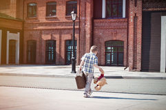 Little kid with suitcase and teddy bear toy crossing the sunny s Royalty Free Stock Photos