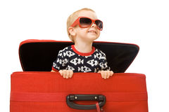 Little kid in sunglasses looking out red suitcase. Isolated on white Royalty Free Stock Images