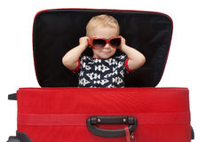 Little kid in sunglasses looking out red suitcase. Isolated on white Royalty Free Stock Photo