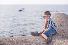 Little kid with sunglasses and striped shirt in front of sea with floating boat Royalty Free Stock Images