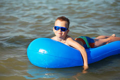 Little kid swimming in the sea on inflatable mattress Stock Images