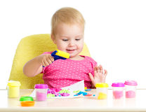 Little kid at table playing with colourful clay Royalty Free Stock Image