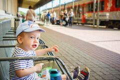 Little kid in a train station  ready to travel again