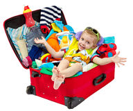 Little kid in travel suitcase packed for vacation. Little kid in travel red suitcase. Packed for vacation in sea resort. Personal belongings: hat, cream, towel Royalty Free Stock Images