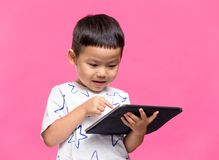 Little kid using dgital tablet. Asian young little boy stock image