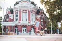 Little kid walking her cocker spaniel, dog in town. Varna theatre, Bulgaria. Little kid walking her cocker spaniel, dog in town royalty free stock photos