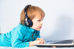 Little kid watching a movie on laptop computer Stock Photography