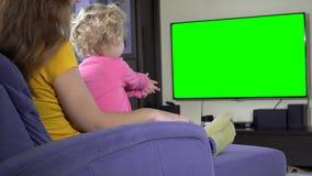 Little kid watching TV program with mom. Green chroma key screen. Static shot. 4K UHD stock footage