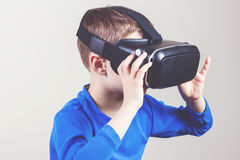 Little kid wearing virtual reality goggles watching movies or playing video games Royalty Free Stock Photos