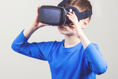 Little kid wearing virtual reality goggles watching movies or playing video games Royalty Free Stock Images
