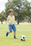 Little kid 7 or 8 years old enjoying happy playing football soccer at grass city park field running and kicking the ball excited i Stock Images