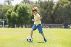 Little kid 7 or 8 years old enjoying happy playing football soccer at grass city park field running and kicking the ball excited i Stock Photos