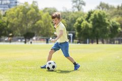 Little kid 7 or 8 years old enjoying happy playing football soccer at grass city park field running and kicking the ball excited i Royalty Free Stock Photography