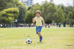 Little kid 7 or 8 years old enjoying happy playing football soccer at grass city park field running and kicking the ball excited i Stock Photo