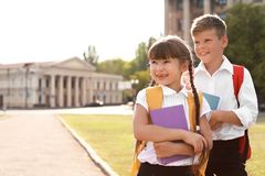 Little kids with backpacks and notebooks outdoors. Stationery for school Stock Images