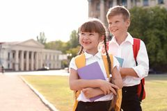 Little kids with backpacks and notebooks outdoors. Stationery for school Stock Image