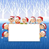 Little Kids with a blank sign and Christmas hats with winter background Stock Image