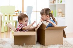 Little kids boy and girl playing in cardboard boxes. Children have fun. stock image