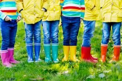 Little kids, boys and girls in colorful rain boots. Close-up of children in different rubber boots, jeans and jackets. Footwear for rainy fall stock photo