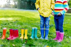 Little kids, boys or girls in jeans and yellow jacket in colorful rain boots. Close-up of children with different rubber boots. Footwear for rainy fall stock photography