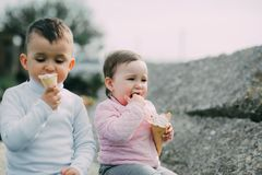 Little kids brother and sister eating ice cream outdoors royalty free stock photos