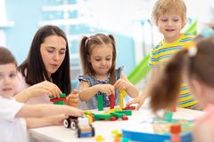 Little kids build block toys at playschool or daycare. Kids playing with color blocks. Educational toys for preschool royalty free stock photography