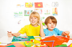 Little kids busy with paper and glue Royalty Free Stock Images