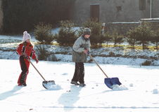 Little kids cleaning ice on pond Royalty Free Stock Photos