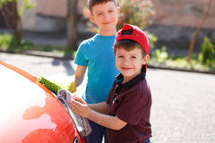 Little kids cleaning red car headlight Stock Photos