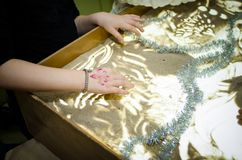 A little kids draws on sand, sand animation, Hands close up.  Royalty Free Stock Photography