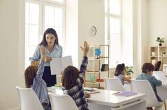 Little school children raise hands willing to answer teacher& x27;s question in class