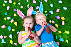 Little kids eating chocolate rabbit on Easter egg hunt. Children on Easter egg hunt. Kids eat chocolate rabbit. Boy and girl relaxing on a green lawn in the Stock Images