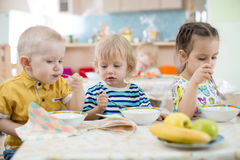 Little kids eating in kindergarten Royalty Free Stock Photos
