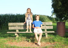 Little kids - girl and boy sitting on a bench Stock Photography