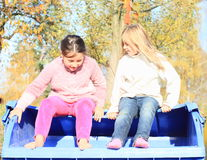 Little kids - girls looking in to container. Two little kids - barefoot girls sitting on the blue container and searching inside Stock Photos