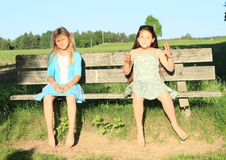 Little kids - girls sitting on a bench Royalty Free Stock Photos