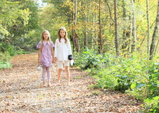 Little kids - girls standing barefoot. Little barefooted kids - girls standing on a path covered with dry leaves with shoes holded in hands stock images