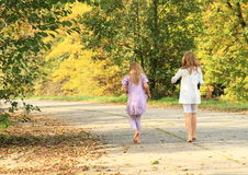 Little kids - girls walking barefoot. Little barefooted kids - girls walking on a concrete road at autumn with shoes holded in hands royalty free stock image