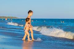 Little kids go to swim in sea water Stock Photo